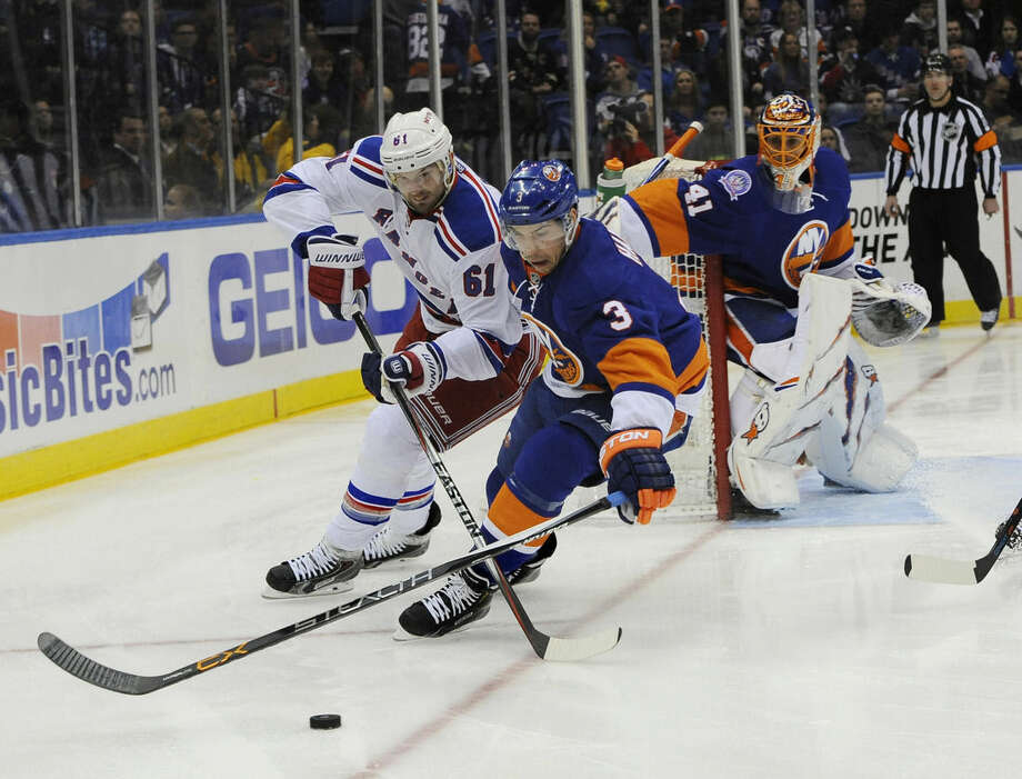 New York Rangers left wing Rick Nash (61) and New York Islanders defenseman Travis Hamonic (3) battle for the puck as New York Islanders goalie Jaroslav Halak (41) defends in the first period of an NHL hockey game Tuesday, March 10, 2015, in Uniondale, N.Y. (AP Photo/Kathy Kmonicek)