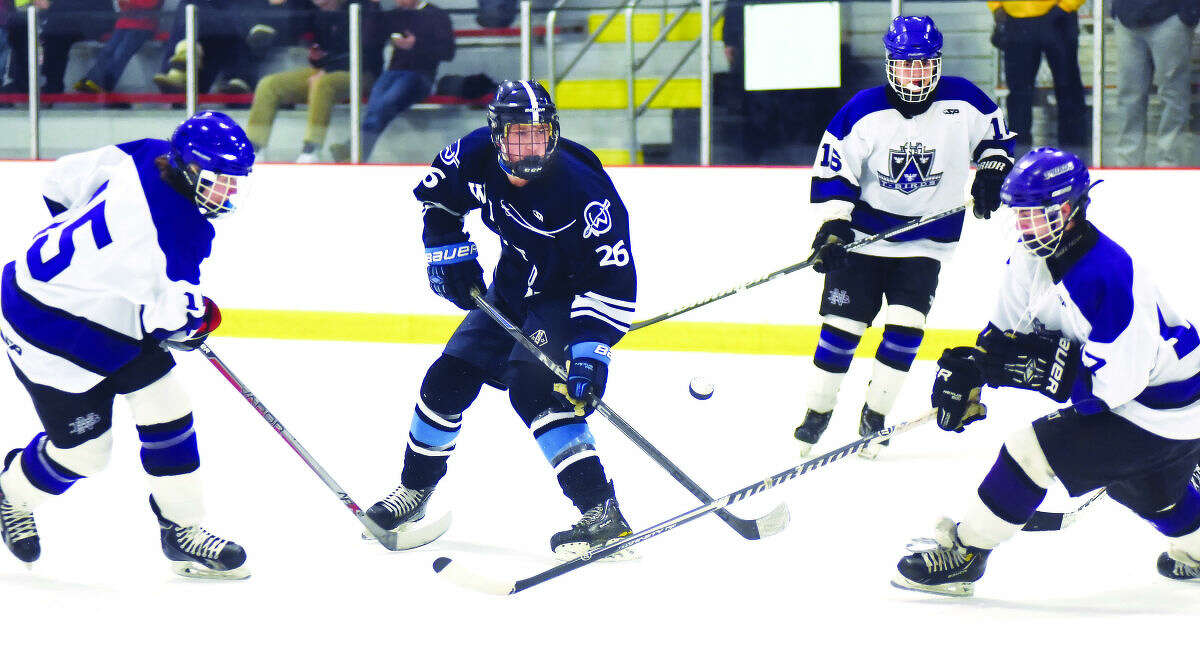Wilton's Ryan Emerson, center, flicks a shot on goal while in the middle of a trio of North Branford defenders. (Hour photo/John Nash)
