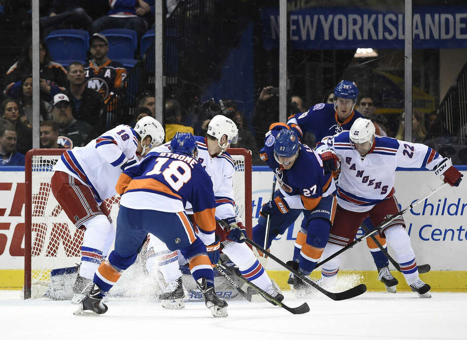New York Islanders center Anders Lee (27) drives the puck past New York Rangers defenseman Dan Boyle (22), right wing Kevin Hayes (13) and defenseman Marc Staal (18) to score past goalie Cam Talbot as Islanders center Ryan Strome (18) looks for the rebound during the first period of an NHL hockey game Tuesday, March 10, 2015, in Uniondale, N.Y. (AP Photo/Kathy Kmonicek)
