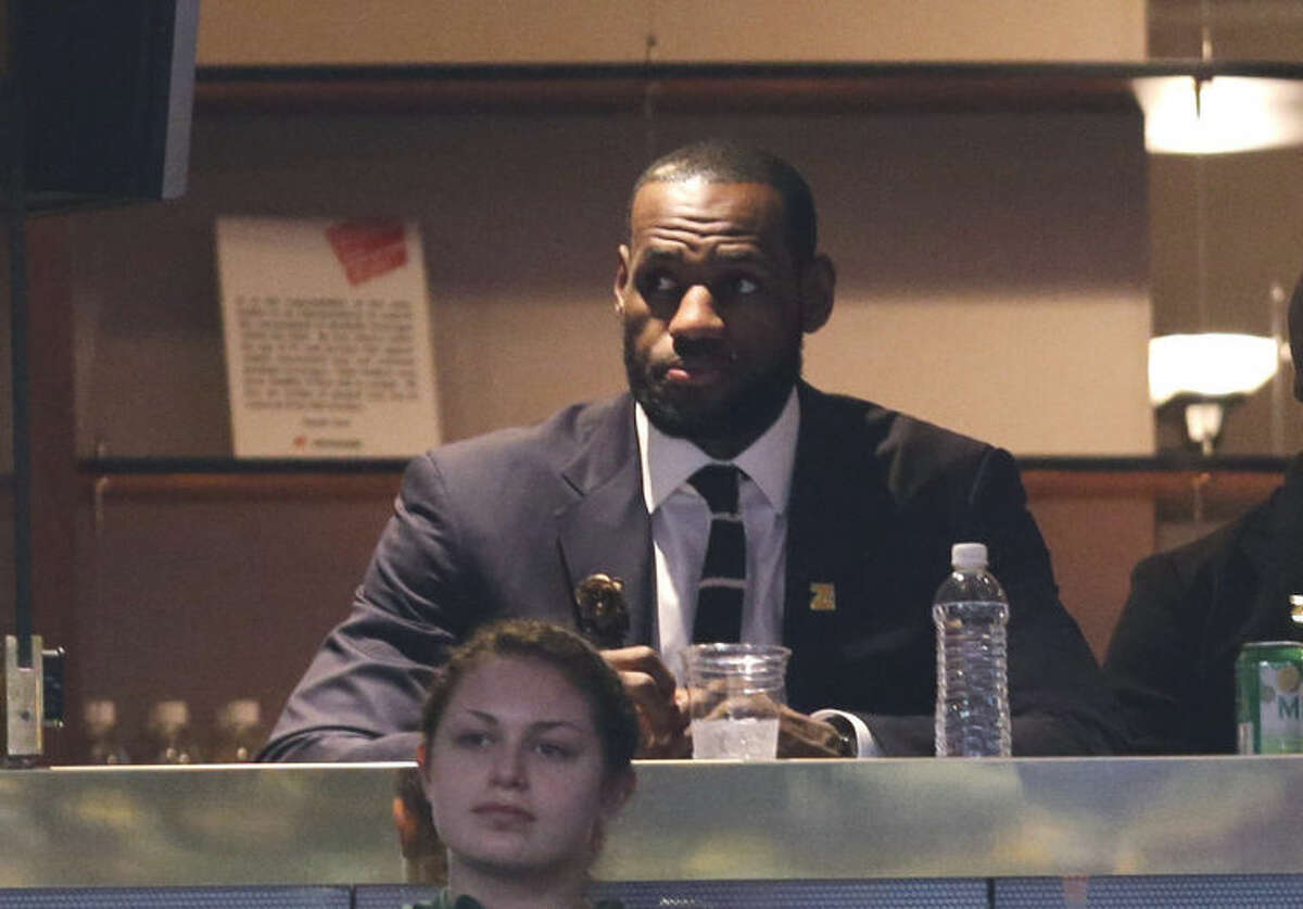 Miami Heat's LeBron James watches an NBA basketball game between the New York Knicks and the Cleveland Cavaliers on Saturday, March 8, 2014, in Cleveland. (AP Photo/Tony Dejak)