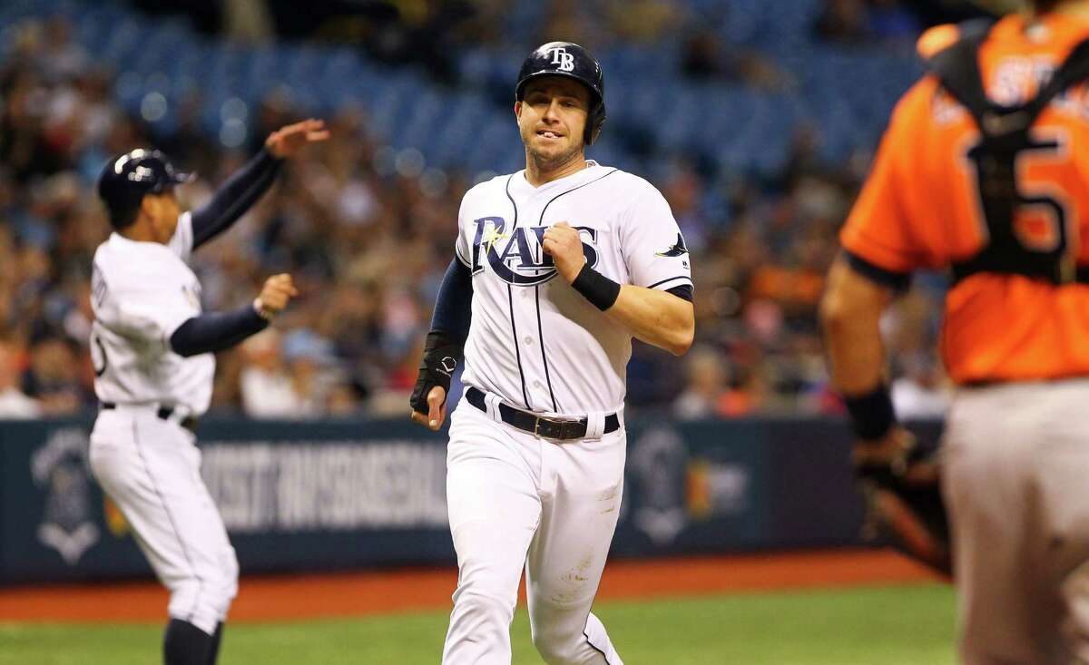 The Tampa Bay Rays' Evan Longoria scores as Rays third base coach Charlie Montoyo, left, waves on runners in the first inning against the Houston Astros at Tropicana Field in St. Petersburg, Fla., on Friday, June 10, 2016.