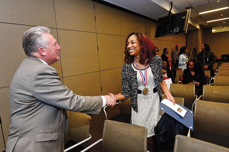 Hour photo / Erik Trautmann Norwalk Mayor harry Rilling offers congratulations to Julia Devalda following the graduation event for DIAGEO's Learning Skills for Life program Wednesday which provides eligible adults with complimentary hospitality and career training.