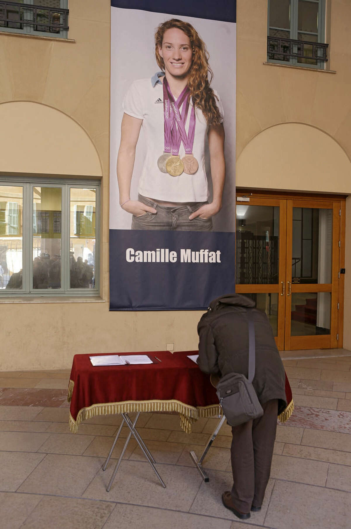 """A woman signs a book of condolence in front of poster of Olympic gold medalist swimmer Camille Muffat, Tuesday, March, 10, 2015, at the City Hall of Nice, southeastern France. Argentine recovery teams arrived March 10 at the site of a helicopter collision to recover the bodies of 10 people, including Muffat, 25, who was participating in the filming of the reality TV survival series """"Dropped"""" when two helicopters collided in mid-air, apparently while filming the show near the town of Villa Castilla in Argentina's La Rioja province. (AP Photo/Lionel Cironneau)"""