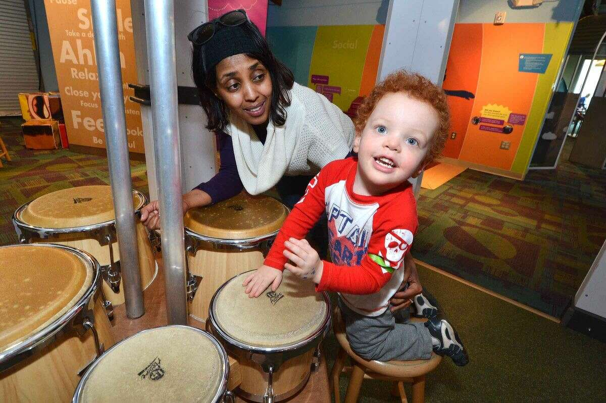 Hour Photo/Alex von Kleydorff Sam Ahmed watches as 2 yr old Riley Lawrence plays on the conga drums during the 15 yr anniversary at Stepping Stones Museum for Children President