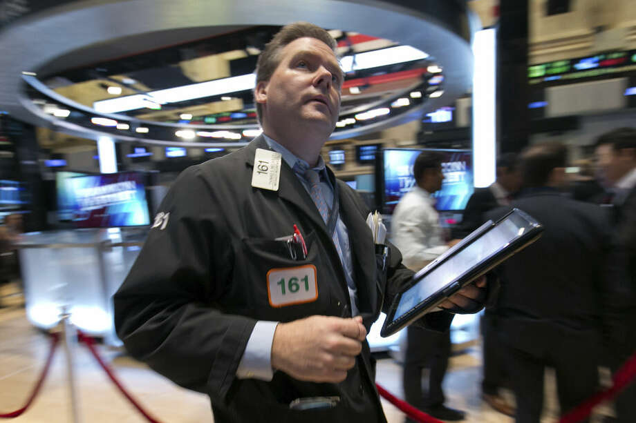 Trader Thomas McCauley works on the floor of the New York Stock Exchange, Wednesday, March 11, 2015. U.S. stock indexes are opening slightly higher, a day after a big sell-off prompted by worries about higher U.S. interest rates. (AP Photo/Richard Drew)