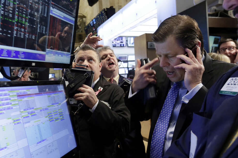 Traders gather at the post that handles MasterCard on the floor of the New York Stock Exchange, Wednesday, March 11, 2015. U.S. stock indexes are opening slightly higher, a day after a big sell-off prompted by worries about higher U.S. interest rates. (AP Photo/Richard Drew)
