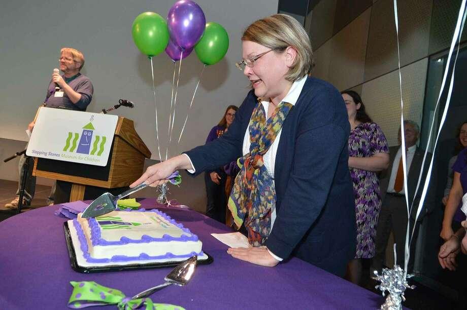 Hour Photo/Alex von Kleydorff Stepping Stones Museum for Children President and CEO Rhonda Kiest cuts the cake celebrating 15 years