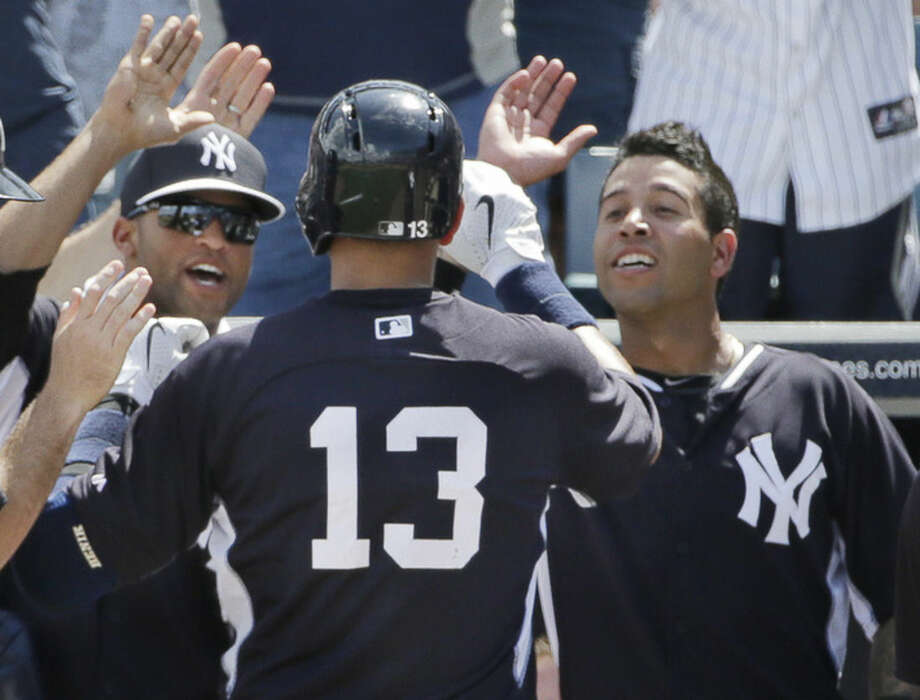 New York Yankees Alex Rodriguez (13) is greeted at the dugout steps after hitting hit his first home run of spring training, a solo blast off Boston Red Sox starting pitcher Brandon Workman, during the fourth inning of a spring baseball game in Tampa, Fla., Wednesday, March 11, 2015. (AP Photo/Kathy Willens)