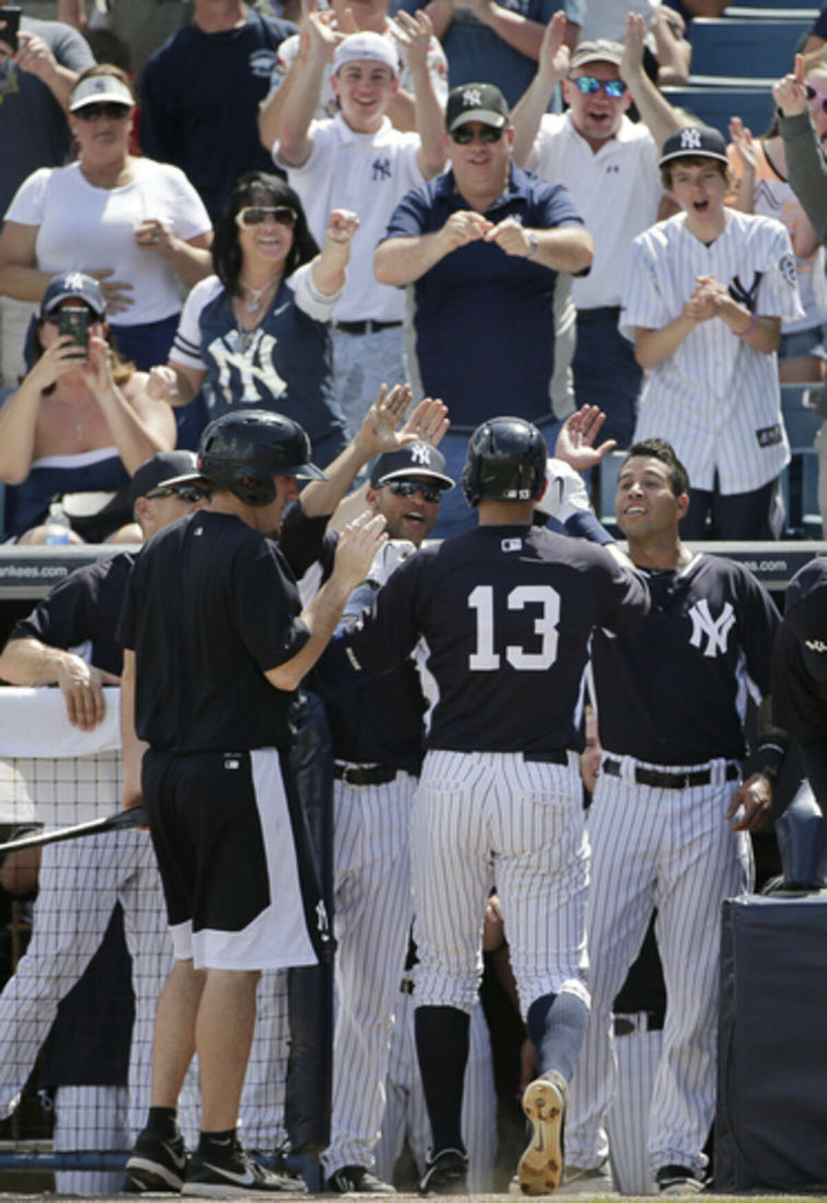 Fans applaud in the stands as New York Yankees manager Joe Girardi, far left, and teammates greet New York Yankees' Alex Rodriguez (13) at the dugout steps after Rodriguez hit his first home run of spring training, a solo blast off Boston Red Sox starting pitcher Brandon Workman, during the fourth inning of a spring baseball game in Tampa, Fla., Wednesday, March 11, 2015. (AP Photo/Kathy Willens)