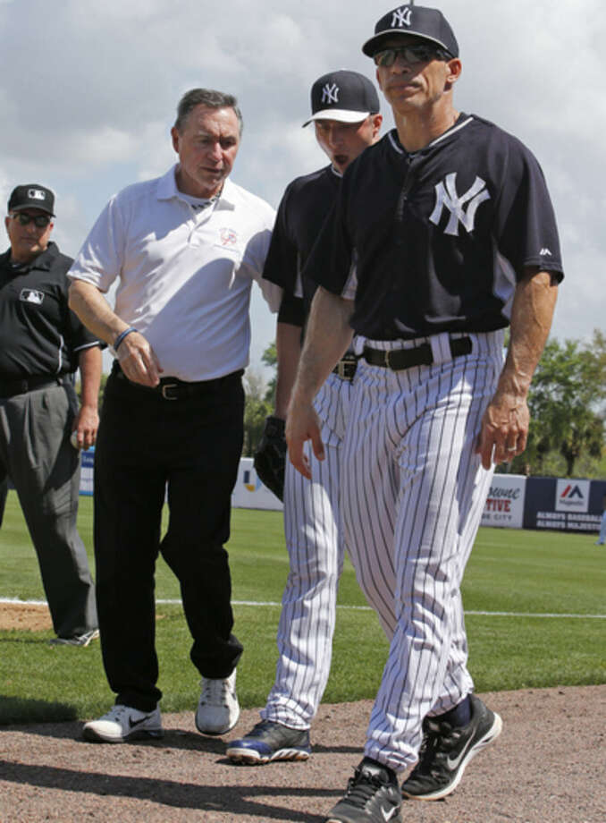 First base umpire Eric Cooper, left, watches,, as New York Yankees trainer Steve Donohue, second from left, and Yankees manager Joe Girardi, right, escort starting pitcher Chris Capuano off the field after Capuano strained his right quadriceps muscle running to first for a putout in the first inning of a spring baseball game against the Boston Red Sox in Tampa, Fla., Wednesday, March 11, 2015. Capuano suffered the injury after facing only his second batter, Brock Holt, in the game. (AP Photo/Kathy Willens)