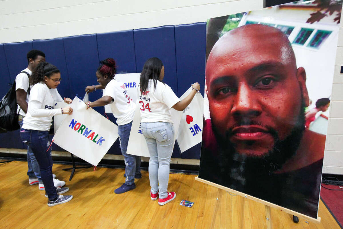 Hour photo/Chris Palermo. Students remove the signs after the memorial ceremony for former Brien McMahon boys basketball coach Mo Tomlin Wednesday evening at Brien McMahon High School.