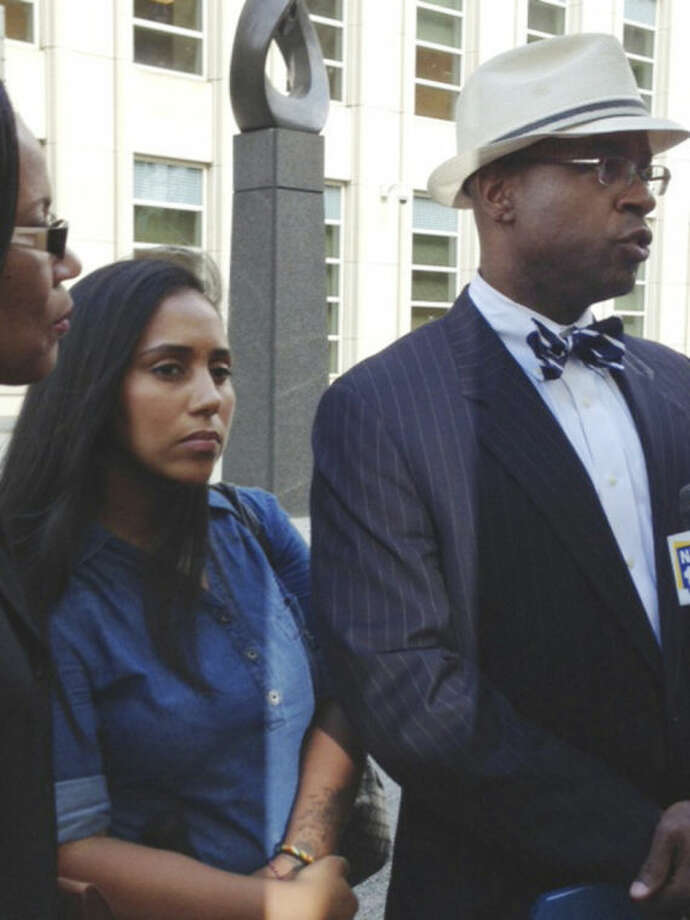 FILE- In this July 3, 2013 file photo, former Metropolitan Detention Center guard, Nancy Gonzalez, center, listens as her attorney, Anthony Rico, speaks to members of the media outside the federal courthouse in the Brooklyn borough of New York. Gonzalez gained notoriety by conceiving a baby behind bars with a cop killer. Although she claims to have had clandestine sexual encounters with at least eight co-workers and a second inmate while on duty at the Metropolitan Detention Center, it remains unclear if anyone else has been disciplined. (AP Photo/Tom Hays, File)