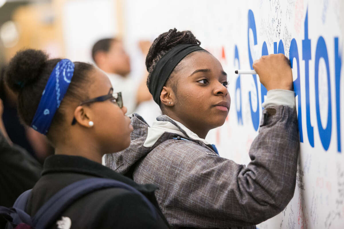 """Hour photo/Chris Palermo. Sophomore Shelcie Charlot signs a memorial banner that read """"Once a Senator, Always a Senator"""" for Mo Tomlin after the memorial ceremony for the former Brien McMahon boys basketball coach Wednesday evening at Brien McMahon High School."""