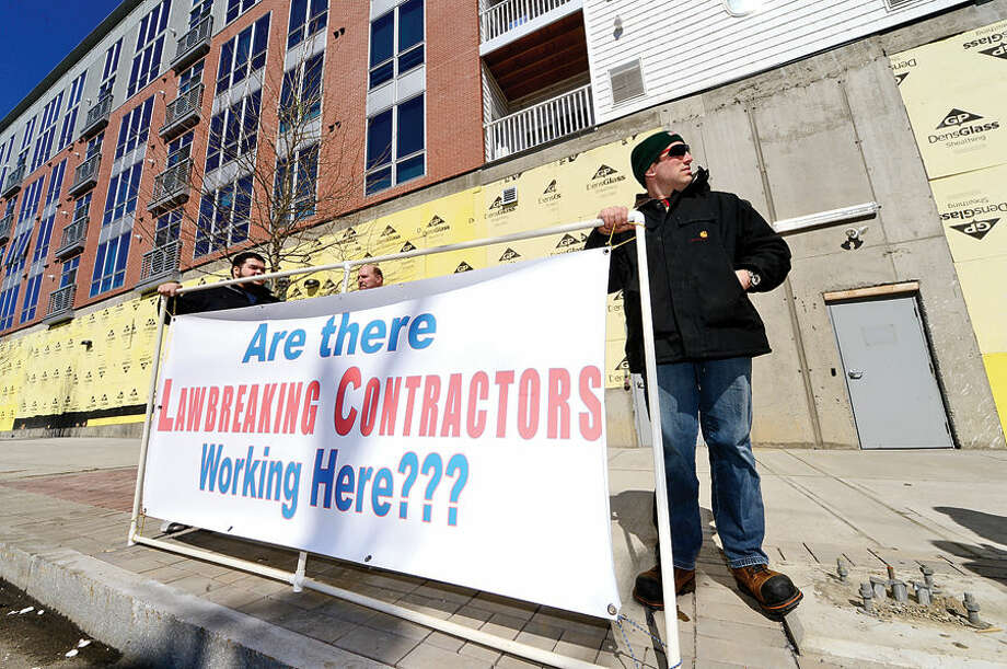 Hour photo / Erik Trautmann New England Regional Council of Carperters Local 210 member Dave Jarvis, Adam Bova and David Valdivinos set up a sign after stop work orders posted by the Connecticut Department of Labor for several contractors engaged in the Waypointe redevelopment project on Orchard St. Thursday.