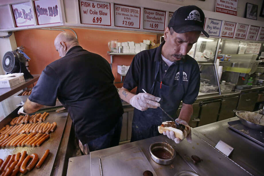 "In this Monday, March 3, 2014 photo manager Jimmy Saccoccio works the grill as Sal O'Brien preps a hot wiener ""all the way"" at Olneyville New York System of Providence in Providence, RI. The James Beard Foundation named the Rhode Island restaurant one of five ""American Classics"" this year as best known for hot wieners, also called hot dogs. (AP Photo/Stephan Savoia)"