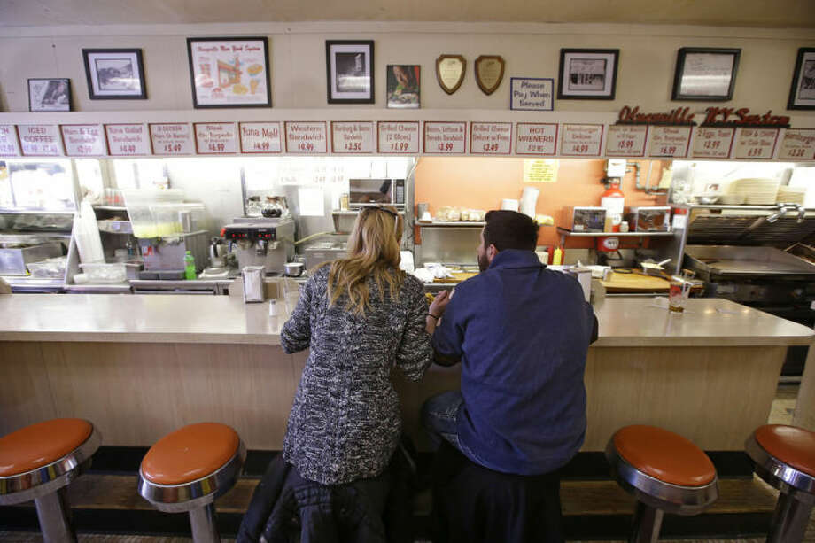 "In this Monday, March 3, 2014 photo Holly Wilson and Ioanni Degaitas eat a lunch of two hot wieners, a loaded cheese burger, a grilled cheese sandwich with bacon and tomato, chile cheese fries, eggs, home fires, coffee milk and black coffee at Olneyville New York System of Providence in Providence, RI. The James Beard Foundation named the Rhode Island restaurant one of five ""American Classics"" this year as best known for hot wieners, also called hot dogs. (AP Photo/Stephan Savoia)"