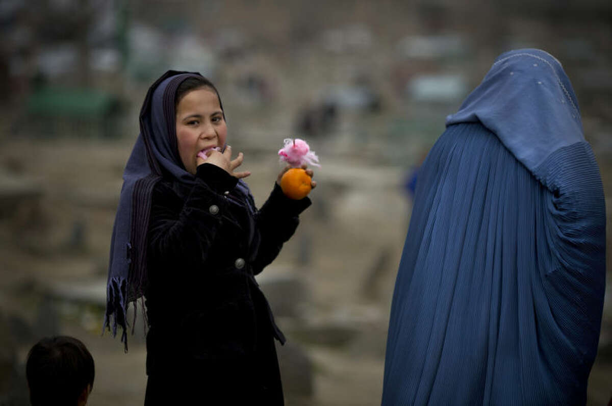 In this Friday, March 7, 2014 photo, an Afghan girl eats cotton candy as she visits with her mother a cemetery in the center of Kabul, Afghanistan. A gender and development specialist and human rights activist, Afghan Wazhma Frogh says her experience characterizes the women?'s rights movement in her country- after 12 years, billions of dollars and countless words emanating from the West commiserating with Afghan women, the successes are fragile, the changes superficial and vulnerable. (AP Photo/Anja Niedringhaus)
