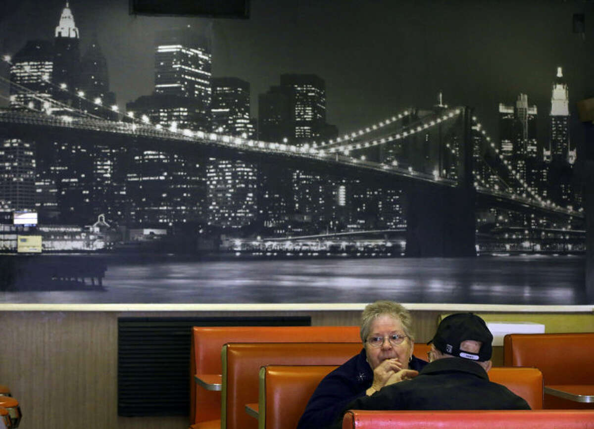 """In this Monday, March 3, 2014 photo Joan Vear and John Iaciofano eat lunch under a mural of New York City's Brooklyn Bridge at Olneyville New York System of Providence in Providence, RI. The James Beard Foundation named the Rhode Island restaurant one of five """"American Classics"""" this year as best known for hot wieners, also called hot dogs. (AP Photo/Stephan Savoia)"""