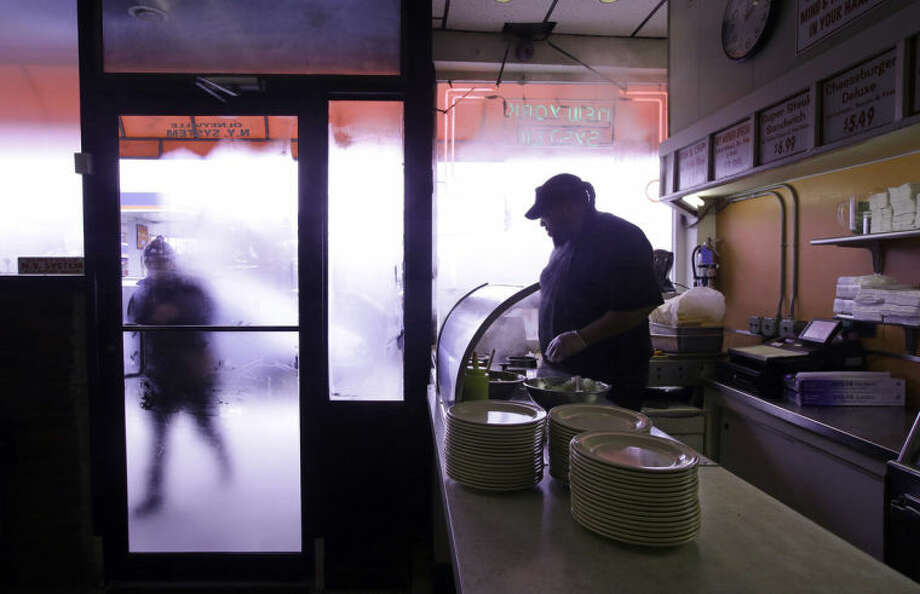 "In this Monday, March 3, 2014 photo Nicholas Barros, a waiter and cook at Olneyville New York System of Providence works the grill as a customer walks up to the door in Providence, RI. The James Beard Foundation named the Rhode Island restaurant one of five ""American Classics"" this year as best known for hot wieners, also called hot dogs. (AP Photo/Stephan Savoia)"