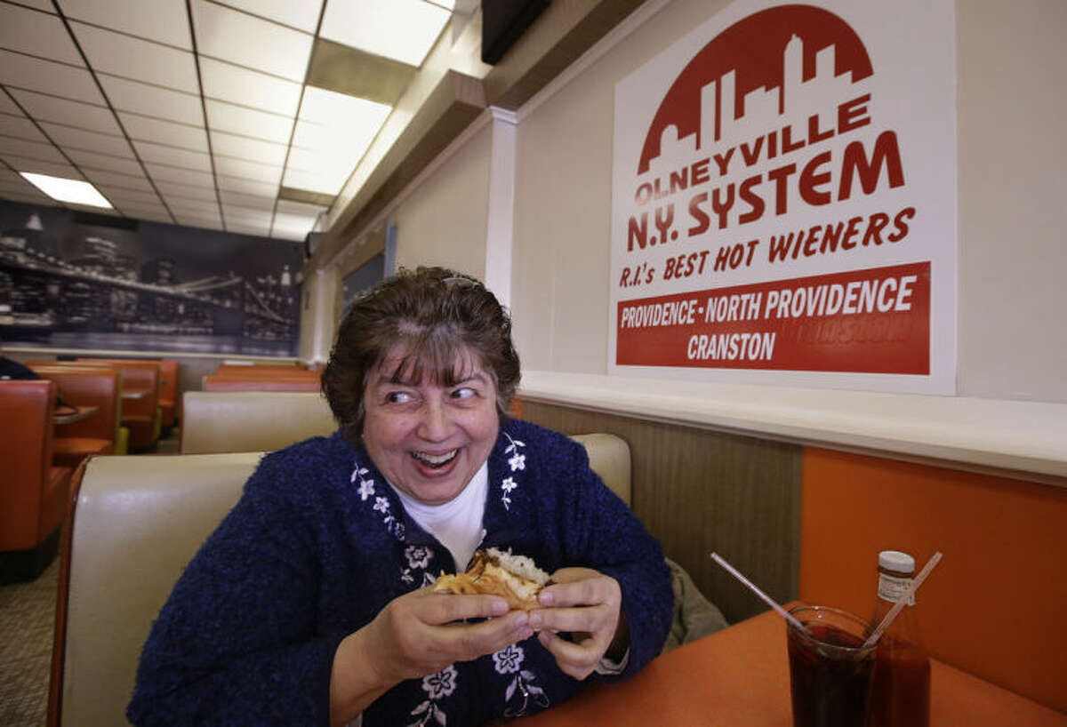 """In this Monday, March 3, 2014 photo Judy Dexter prepares to take a bit of her hot wiener """"all the way"""" at Olneyville New York System of Providence in Providence, RI. The James Beard Foundation named the Rhode Island restaurant one of five """"American Classics"""" this year as best known for hot wieners, also called hot dogs. (AP Photo/Stephan Savoia)"""