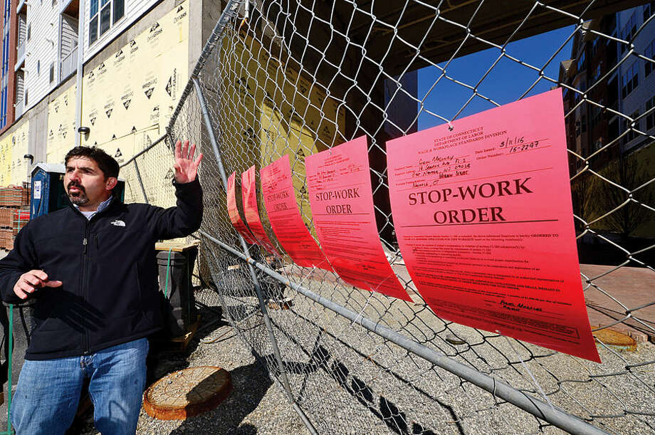 Hour photo / Erik Trautmann Ted Duarte, Senior Organizer for New England Regional Council of Carperters, points out the stop work orders posted by the Connecticut Department of Labor for several contractors engaged in the Waypointe redevelopment project on Orchard St. Thursday.