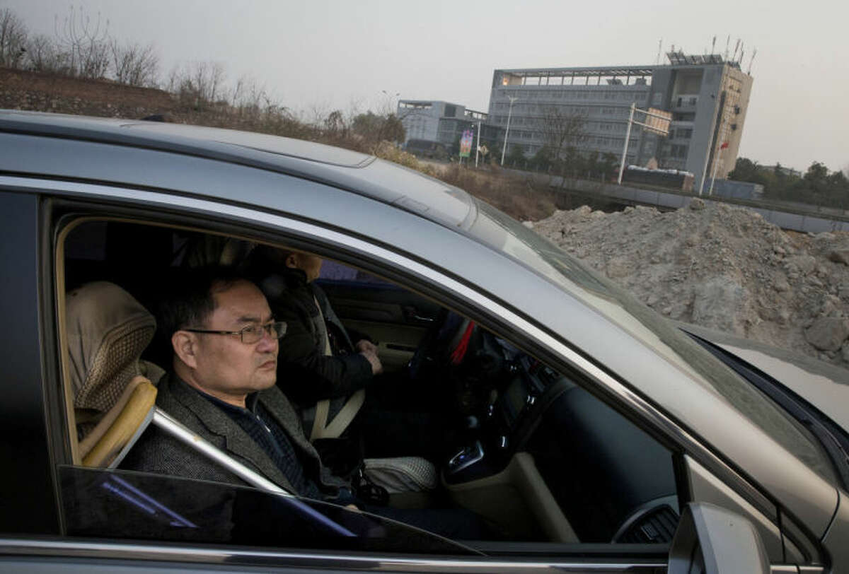 In this Monday, Jan. 20, 2014 photo, Zhou Wangyan, head of the Liling city land resources bureau, sits in a car in Zhuzhou city in central China's Hunan province across the road from Qiaotoubao, a Communist Party detention center where he says interrogators tortured him for months in 2012 and broke his leg while trying to force him to confess to bribery. (AP Photo/Andy Wong)