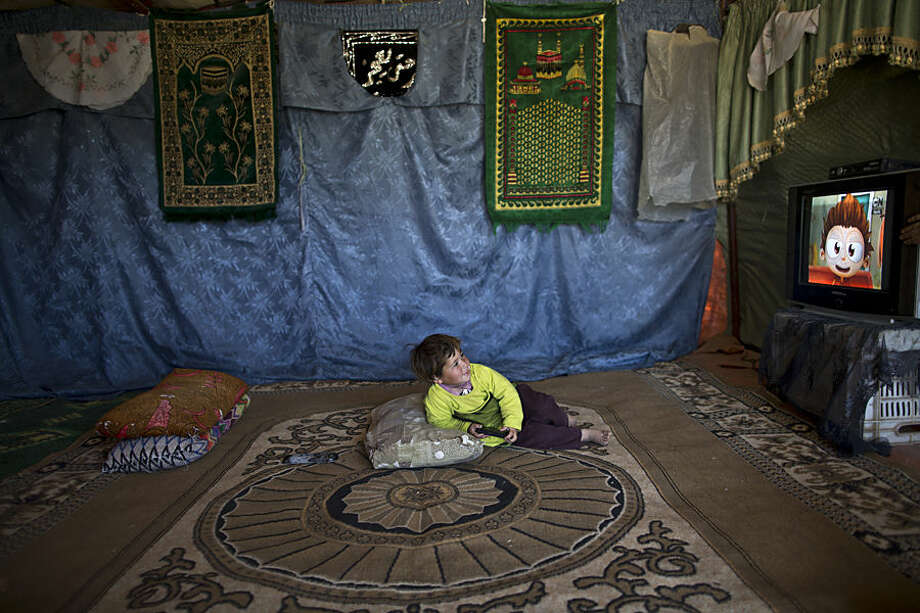In this Friday, March 6, 2015 photo, Syrian refugee Hazar Al-Hassan, 3, watches cartoons inside her family's tent at an informal tented settlement in the Jordan Valley, Jordan. In June 2014, a survey commissioned by UNICEF said there were 125 informal tent settlements for Syrian refugees across Jordan, home to some 10,000 people. The survey said nearly 80 percent there were younger than 18. (AP Photo/Muhammed Muheisen)