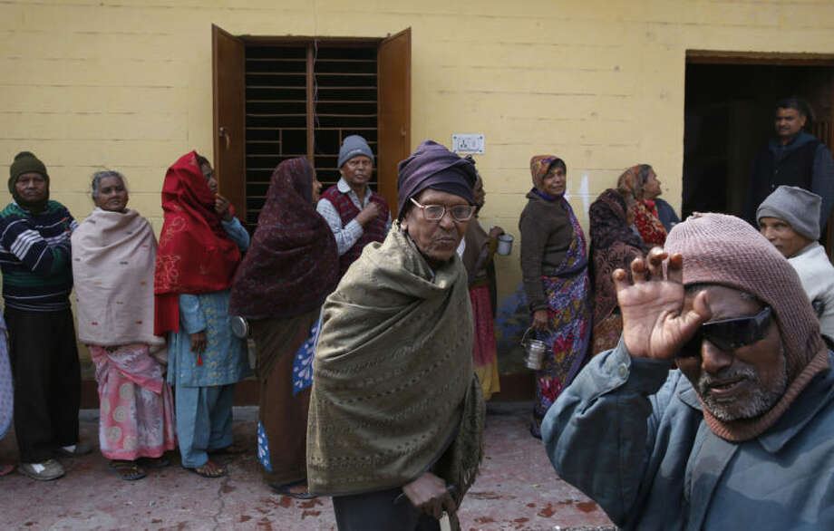 In this Feb. 16, 2014 photo, Indian men and women suffering from leprosy wait in a queue for food at a leper colony in New Delhi, India. The stigma of leprosy endures in India, even though the country has made great strides against the disease, which is neither highly contagious nor fatal. Now the number of new annual cases has risen slightly after years of steady decline, and medical experts say the enormous fear surrounding leprosy is hindering efforts to finally eliminate it. (AP Photo/Manish Swarup)