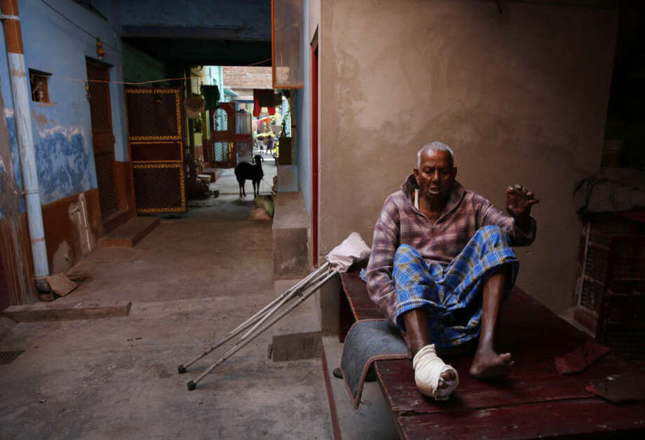 In this Feb. 5, 2014 photo, Leprosy-affected Jaffar Ali, 75, makes an effort to get up from his cot outside his house at a leper colony in New Delhi, India. Although India has made great strides against leprosy over the years, the stigma of the disease is as intractable as ever, hindering efforts to eliminate the disease entirely. Worldwide the number of new leprosy patients has dropped from around 10 million in 1991 to around 230,000 last year. Of these, 58 percent were to be found in India, according to the World Health Organization. (AP Photo/Manish Swarup)