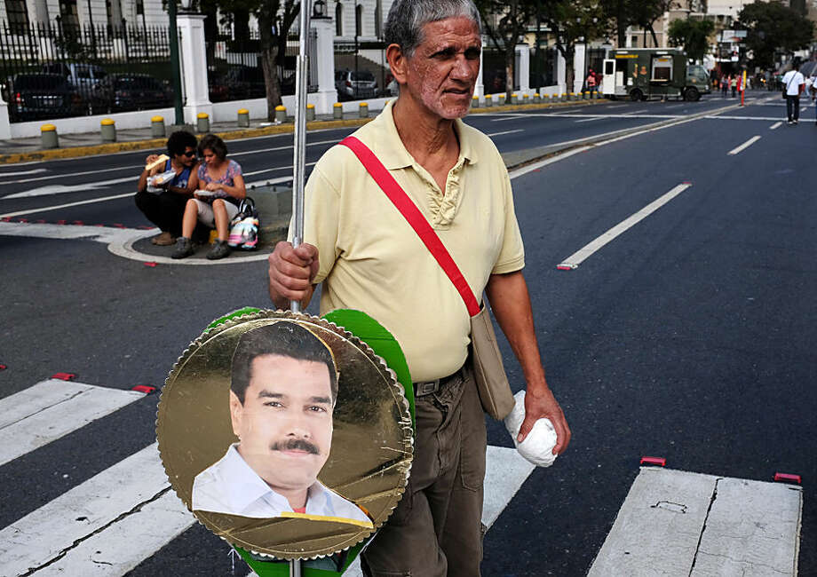 "A supporter of Venezuela's President Nicolas Maduro walks with an image of the leader to a rally outside Miraflores presidential palace in Caracas, Venezuela, Thursday, March 12, 2015. Venezuela's Congress has approved Maduro's request for expanded powers, which he says he needs to protect the socialist South American country from U.S. ""imperialism."" Maduro's request to enact laws for up to six months without consulting Congress was given initial approval by lawmakers Tuesday and is expected to gain final approval Sunday. (AP Photo/Fernando Llano)"