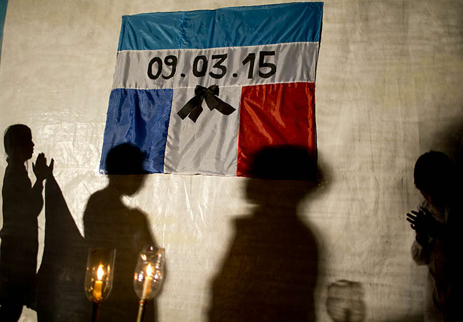 "The shadows of children are cast on a tarp displaying the flags of Argentina and France, combined, and the date of the fatal helicopter crash, during a silent march to honor the crash victims in Villa Castelli, in the La Rioja province of Argentina, Thursday, March 12, 2015. Residents who thought their town would become known for the filming of the popular European reality show ""Dropped"" are now coping with the tragedy of 10 people from the show being killed when two helicopters collided in midair and crashed on Monday. (AP Photo/Natacha Pisarenko)"