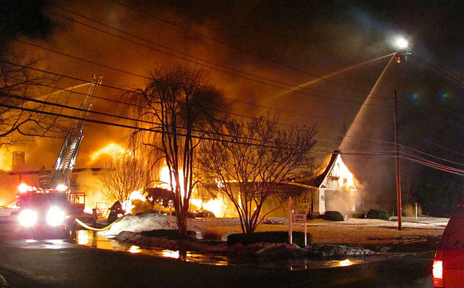 Firefighters try to put out a fire at the main clubhouse of the Madison Country Club Thursday morning, March 12, 2015, in Madison, Ohio. Fire officials say crews from more than 20 departments and three counties were called to help fight the flames. Officials say the fire spread quickly and the building is considered to be a complete loss. (AP Photo/The Plain Dealer, Cliff Pinckard) MANDATORY CREDIT; NO SALES