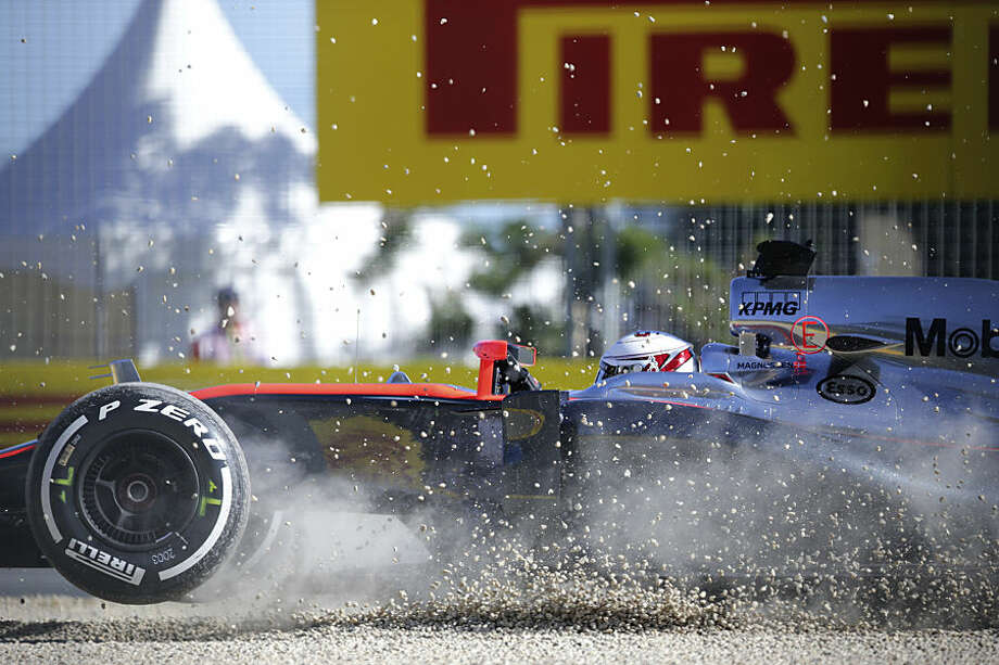 McLaren driver Kevin Magnussen of Denmark steers his car on the dirt on his way to crashing into a tire wall during the second practice session for the Australian Formula One Grand Prix at Albert Park in Melbourne, Australia, Friday, March 13, 2015. (AP Photo/Rob Griffith)