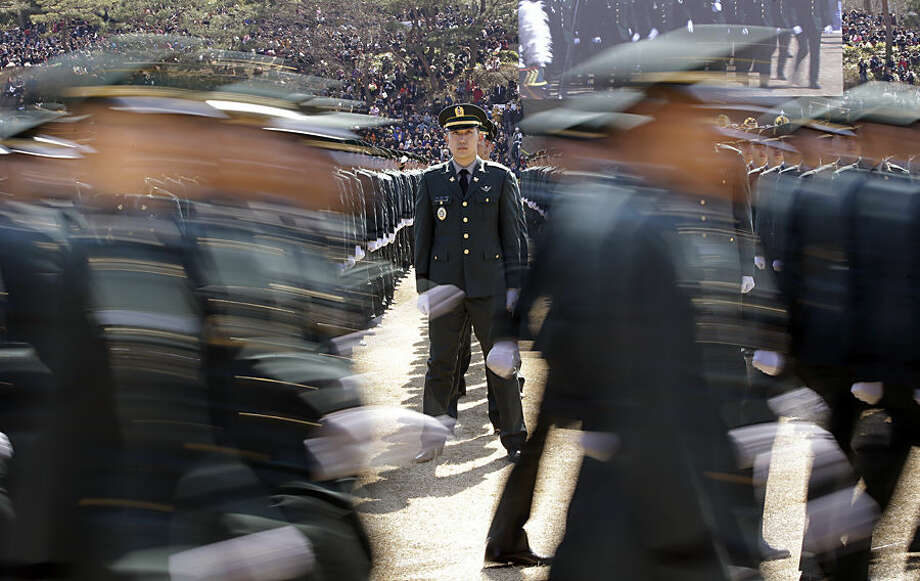 A new South Korean military officer, center, stands still as other officers march during the joint commission ceremony of over 6,478 new military officers of the army, navy, air force and marines at the military headquarters in Gyeryong, south of Seoul, South Korea Thursday, March 12, 2015. (AP Photo/Lee Jin-man)