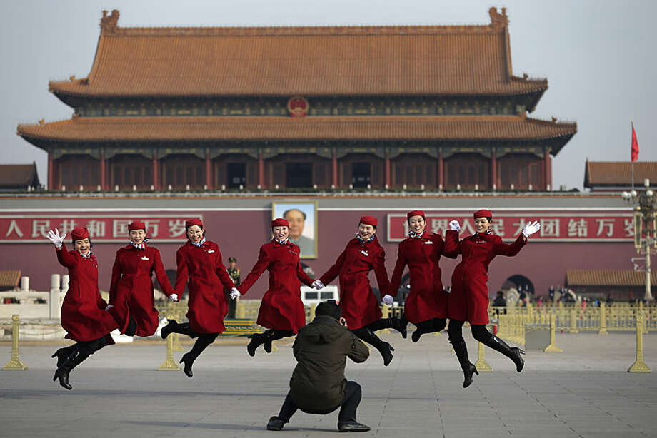 Chinese hostesses, who serve the delegates of the National People's Congress, jump as they pose for photographs on Tiananmen Square during a plenary session of the NPC held at the Great Hall of the People in Beijing Thursday, March 12, 2015. Thousands of delegates from across the country are in the Chinese capital to attend the annual National People's Congress and the Chinese People's Political Consultative Conference. (AP Photo/Andy Wong)