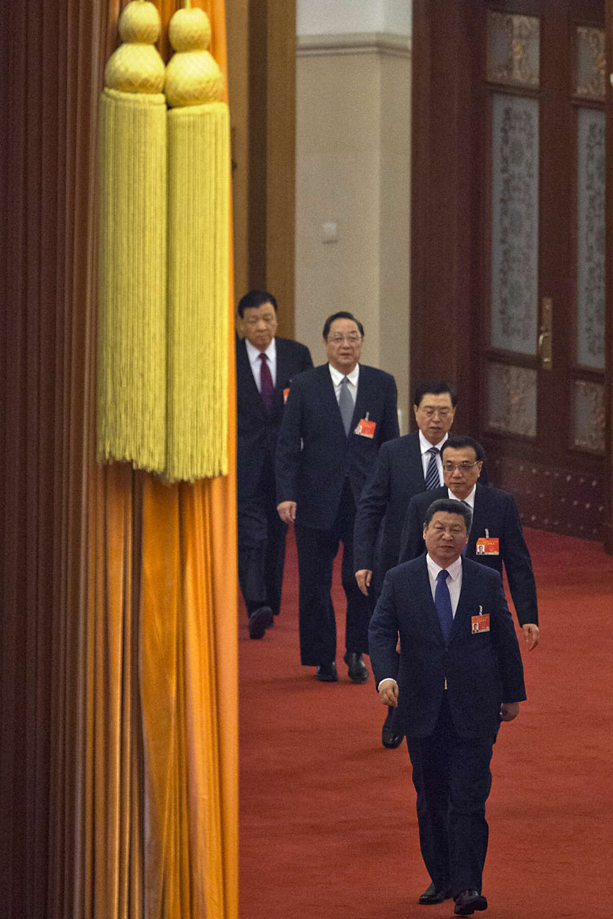 Chinese President Xi Jinping, front, leads the members of the Politburo Standing Committee as they arrive for a plenary session of the National People's Congress in the Great Hall of the People in Beijing Thursday, March 12, 2015. Behind Xi is Chinese Premier Li Keqiang and Politburo members Zhang Dejiang, Yu Zhengsheng and Liu Yunshan. (AP Photo/Ng Han Guan)