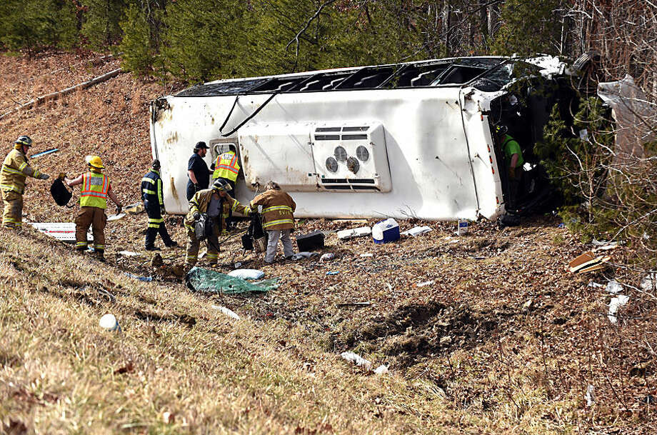 Emergency responders work to clear the wreckage of a southbound charter bus which left the Interstate 65 roadway just North of Henryville, Ind., Thursday, March 12, 2015. The bus was carrying members of a college bowling team en route to a tournament in Tennessee. (AP Photo/News and Tribune, Tyler Stewart)