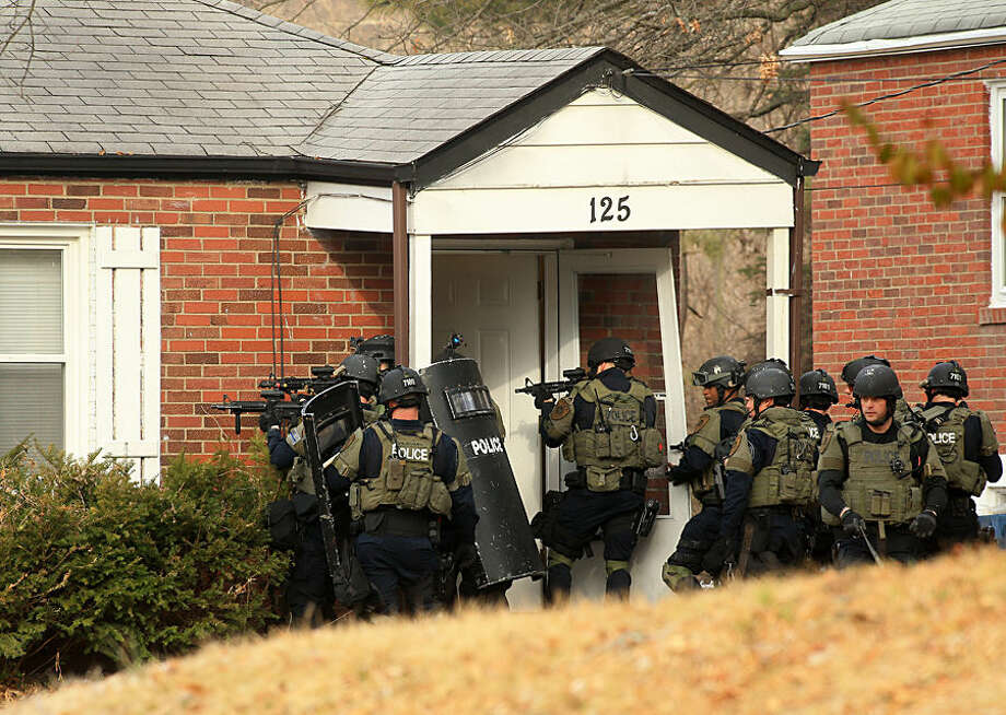 "A police tactical team prepares to enter a home on Dade Avenue, in Ferguson, Mo., on Thursday, March 12, 2015, as they search for a suspect they believe to be in the attic as they continue investigating the shooting of two police officers during protests earlier in the day. The two officers were shot in front of the Ferguson Police Department while demonstrators were gathered across the street, an attack the county police chief described as ""an ambush"" that could easily have killed both men. (AP Photo/St. Louis Post-Dispatch, Christian Gooden)"