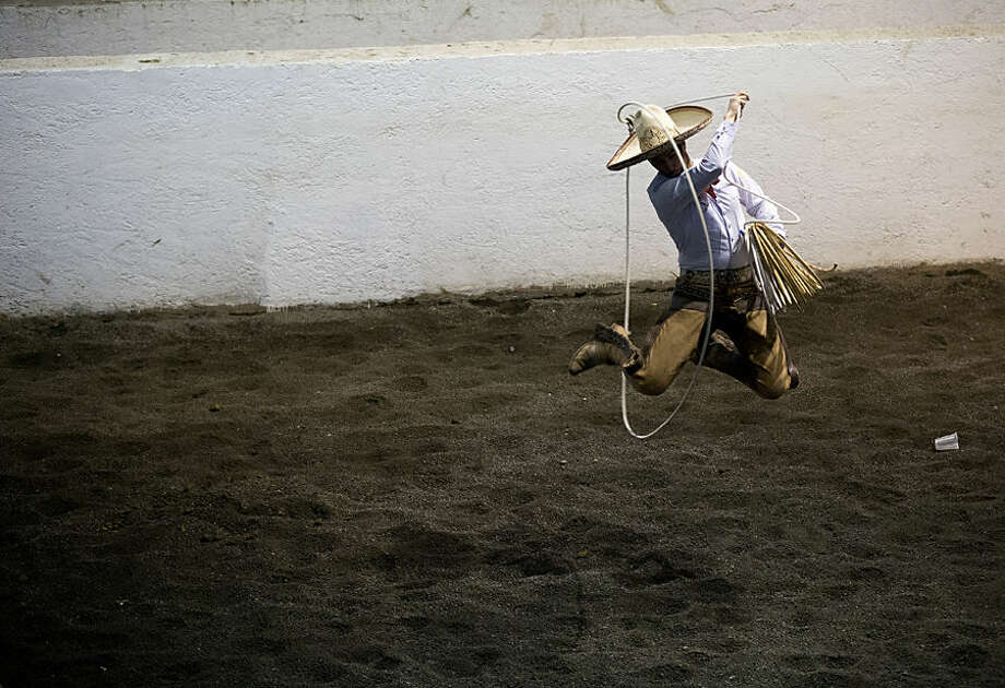 In this Feb. 26, 2015 photo, Charro Carlos Maurer, from Puebla, practices his lasso skills ahead of the roping events, during a charreada in Mexico City. In team roping, charros must lasso both the neck and the hind legs of a bull, while in horse roping a charro on foot must capture a wild horse by roping its front legs. Extra points are awarded for rope tricks. (AP Photo/Rebecca Blackwell)
