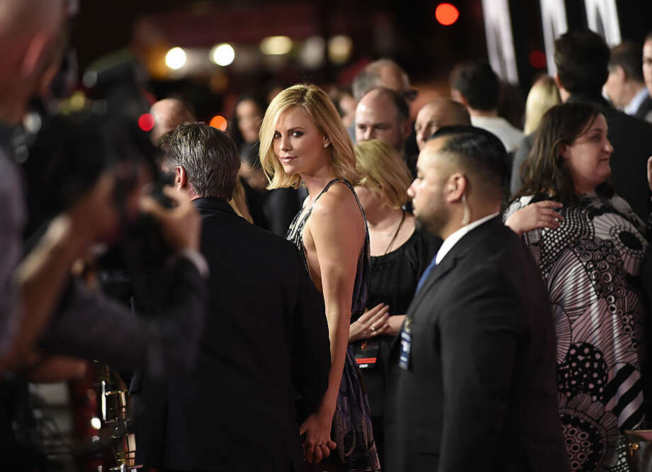 """Charlize Theron arrives at the Los Angeles premiere of """"The Gunman"""" at Regal Cinemas LA LIVE on Thursday, March 12, 2015. (Photo by Chris Pizzello/Invision/AP)"""