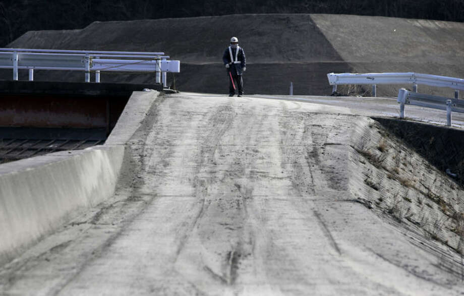In this Tuesday, March 4, 2014 photo, a worker stands on an intersection of a make-shift access road leading to construction sites in Otsuchi, Japan. Construction has only begun at two of 10 planned sites in Otsuchi and further down the coast. (AP Photo/Junji Kurokawa)