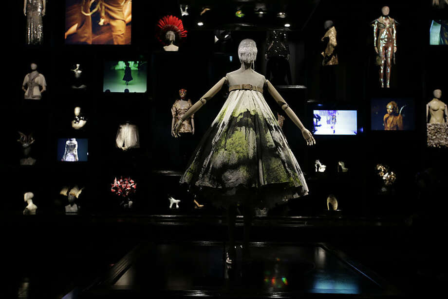 A dress worn by model Shalom Harlow, who became became a human canvas at Alexander McQueen's 13th fashion show in September 1998, as robotic arms spray painted her tulle dress, which is one of the major items on display at the Alexander McQueen exhibition 'Savage Beauty' at the Victoria and Albert museum in London, Thursday, March, 12, 2015. (AP Photo/Alastair Grant)