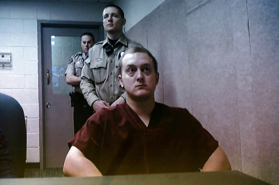 Adam Dees is pictured on a video screen during an arraignment at the Ada County Courthouse in Boise, Idaho Thursday March 12, 2015. Bond was set at $2 million for Adam Dees, based upon his possible involvement in the murders of Theodore, Delores and Thomas Welp. Dees is currently charged with three counts of grand theft, three counts of forgery and a single count of possessing a concealed weapon. (AP Photo/The Idaho Statesman, Kyle Green)