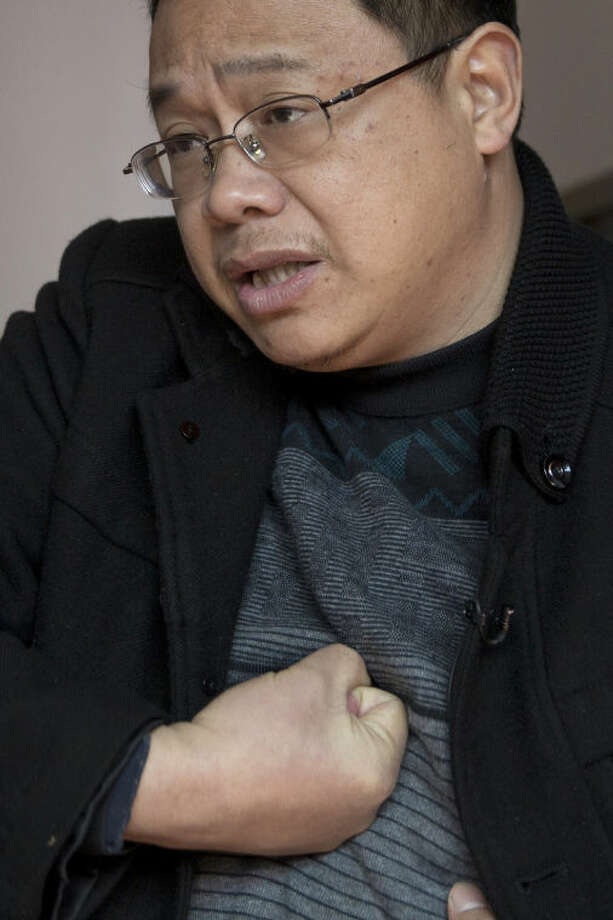 """ADVANCE FOR USE MONDAY, MARCH 10, 2014 AND THEREAFTER - In this Tuesday, Jan. 21, 2014 photo, Xiao Yifei, former deputy head of an industrial park in Ningyuan county, shows how he was punched by Communist Party anti-graft investigators in 2012, during an interview in Changsha in central China's Hunan province. The party defines """"shuanggui"""" as an order to its officials to appear at a designated time and place to account for their actions. Party anti-corruption experts acknowledge that the practice is legally problematic but say it's indispensable in fighting corruption. (AP Photo/Andy Wong)"""