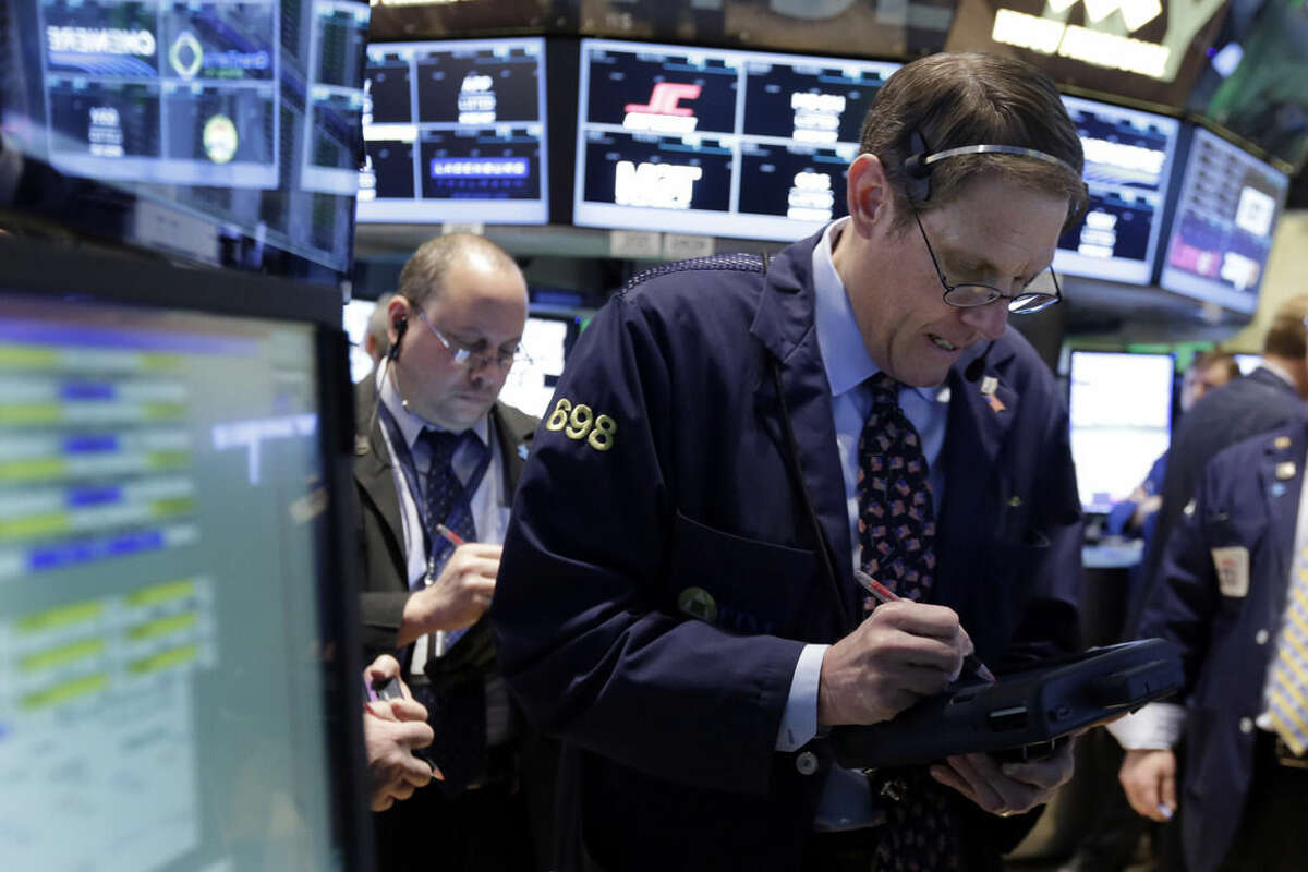 Trader Luke Scanlon, right, works on the floor of the New York Stock Exchange, Friday, March 13, 2015. U.S. stocks are opening slightly lower a day after the market notched its best performance in five weeks. (AP Photo/Richard Drew)