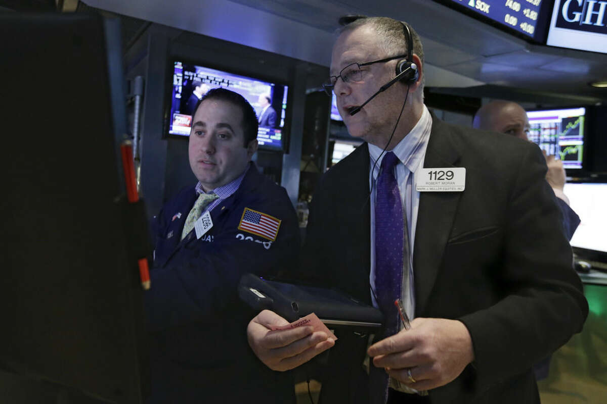 Trader Robert Moran, right, works on the floor of the New York Stock Exchange, Friday, March 13, 2015. U.S. stocks are opening slightly lower a day after the market notched its best performance in five weeks. (AP Photo/Richard Drew)