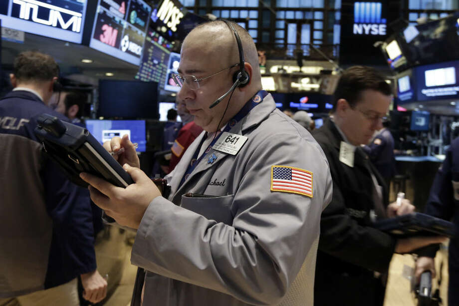 Trader Michael Capolino, center, works on the floor of the New York Stock Exchange, Friday, March 13, 2015. U.S. stocks are opening slightly lower a day after the market notched its best performance in five weeks. (AP Photo/Richard Drew)