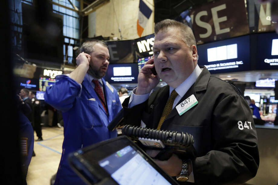 Traders Kevin Lodewick, left, and George Ettinger work on the floor of the New York Stock Exchange, Friday, March 13, 2015. U.S. stocks are opening slightly lower a day after the market notched its best performance in five weeks. (AP Photo/Richard Drew)