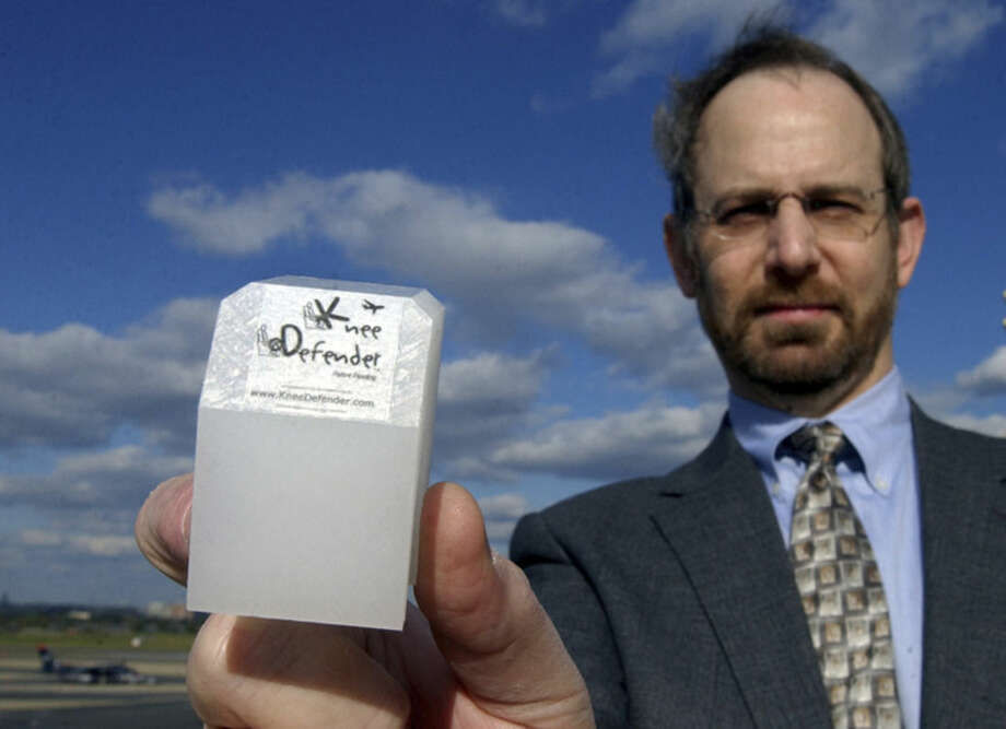 "FILE - In this Oct. 23, 2003 file photo, Ira Goldman poses with with his invention, the Knee Defender, at Washington's Reagan National Airport. ""Sales went off the charts,"" says Goldman, after a midair brawl broke out in the summer of 2014 when a man used the device to stop a woman in front of him from reclining her seat. (AP Photo/Susan Walsh, File)"