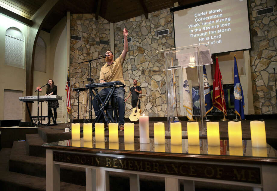 Associated pastor Trey Rose holds up his hand as a candlelight memorial service honoring victims in an Army UH-60 Black Hawk helicopter crash is held Wednesday evening, March 11, 2015, at Navarre First Assembly of God in Navarre, Fla. Simultaneously, the search was continuing for any survivors after the Tuesday night crash off the Florida Panhandle. Seven Marines and four members of the Louisiana National Guard were on a routine nighttime training mission at Eglin Air Force Base. (AP Photo/AL.com, Mike Brantley)
